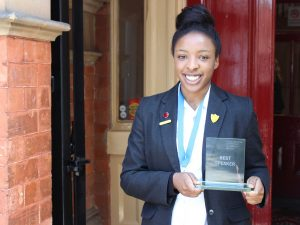 Nathania-with-her-award-for-Best-Speaker-outside-Red-House-School