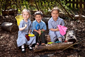 Three children sat on a log in the nursery garden holding nets and a magnifying glass
