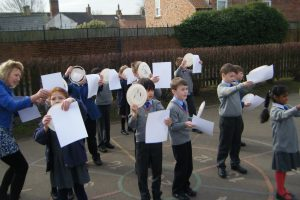 Pupils safely observe the shadow of the moon covering the sun