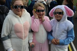 Red House School pupils dressed as Easter bunnies view the Solar Eclipse through protective glasses