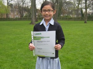Pupil-holding-holding-their-LAMDA-certificate-who-achieved-100 percent-pass-rate
