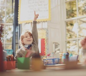 girl with her hand in the air sat at a classroom desk