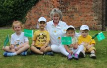 A group of children sat holding Daisy Chain charity flags getting ready for the jogathon race