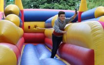 pupil running on an inflatable at the summer garden fete
