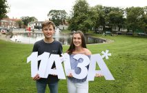 two pupil celebrate their amazing GCSE results by holding A* cut out letters