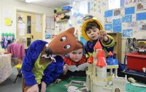 Three children at the Nursery & Infant school are dressed up in costumes for World Book Day