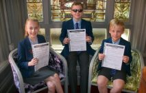 3 Red House School pupils are sat together holding their certificates. They were all winners of the ISA Essay competition