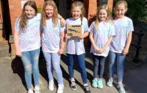 five pupils stide the entrance to Red House School holding the winners plaque from the Winners of the North East Jaguar Primary School Challenge