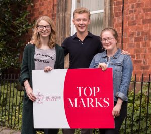 Three pupils hold a sign saying Top Marks on their GCSE results day outside of Red House School in Norton, Stockton on Tees