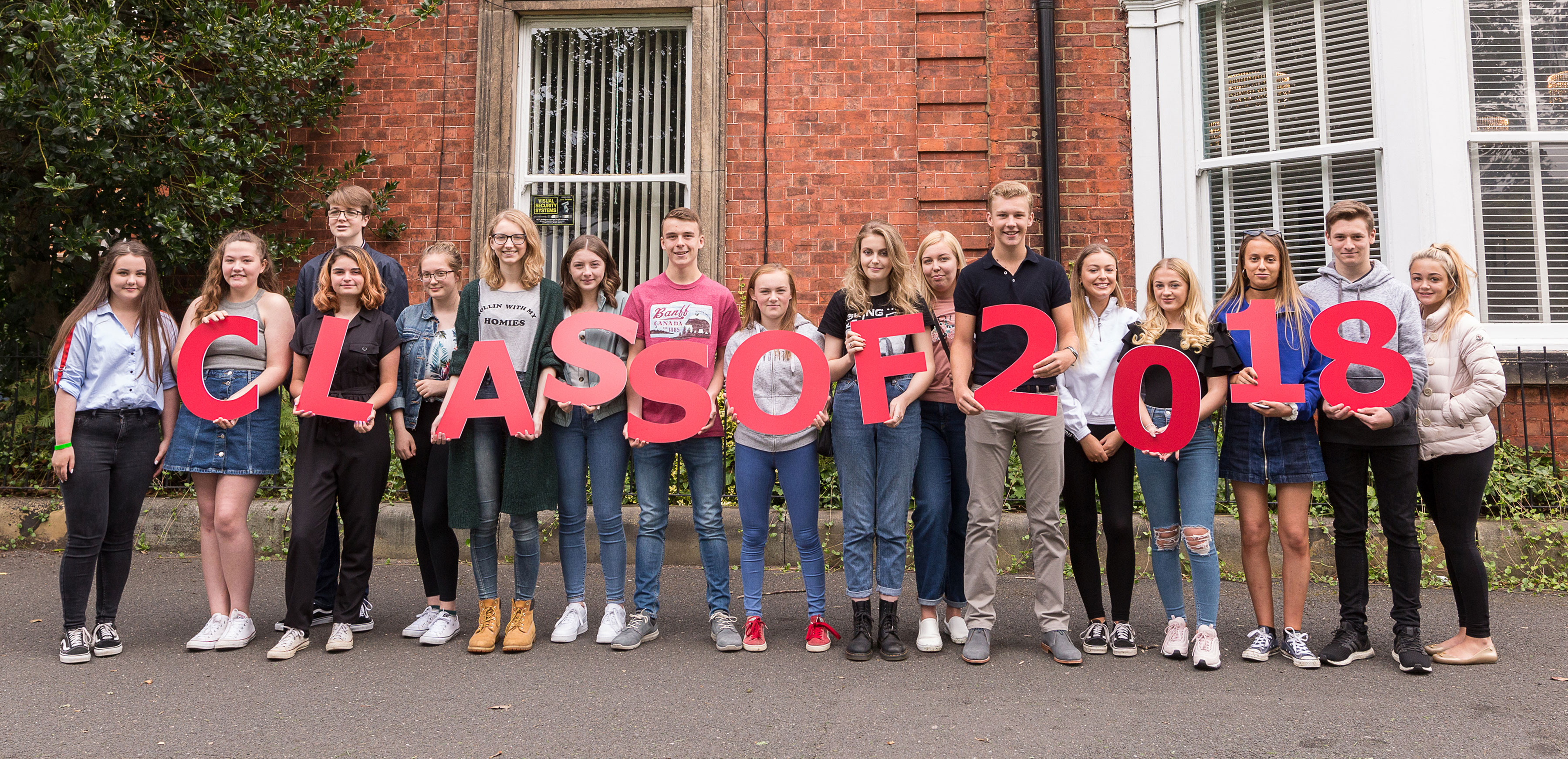 a group of pupils hold letters spelling the words class of 2018 on their GCSE results day whilst standing outside Red House School in Norton, Stockton on Tees