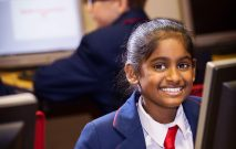 A Red House School pupil is smiling whilst sat at her computer. In the background is another pupil working on his computer.
