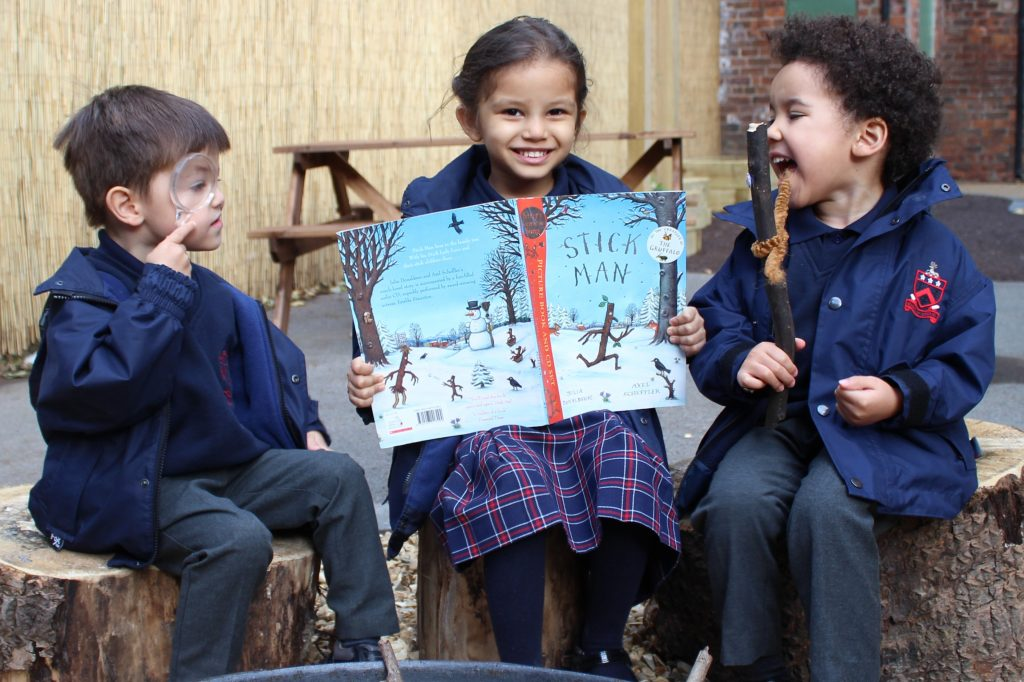 Three children sat on logs in the outdoor classroom reading the book called Stick Man