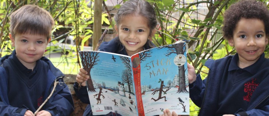 Three Red House School pupils siting on logs outside in the Nursery garden reading the book Stick Man