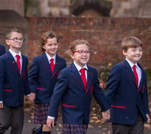 Four Red House School children walking in a line holding hands