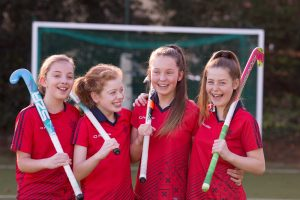 Group of four girls stood together laughing and holding hockey sticks