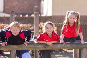 Three Red House pupils playing on wooden equipment in the Junior School playground