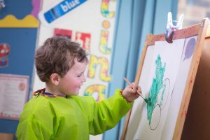 Red House pupil stood painting a picture in Nursery