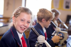 Three pupils looking into microscopes during their Biology lesson