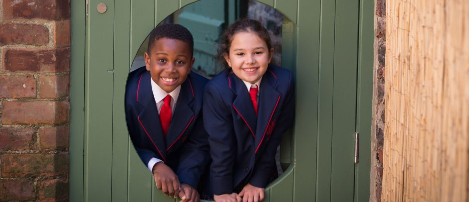 Two Red House pupils looking though the door leading to the outdoor classroom