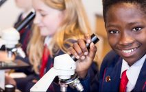 Two Red House School pupils looking into microscopes in their biology lesson