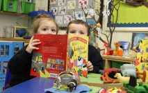 Two Red House pupils peering over the top of What the Ladybird Heard book