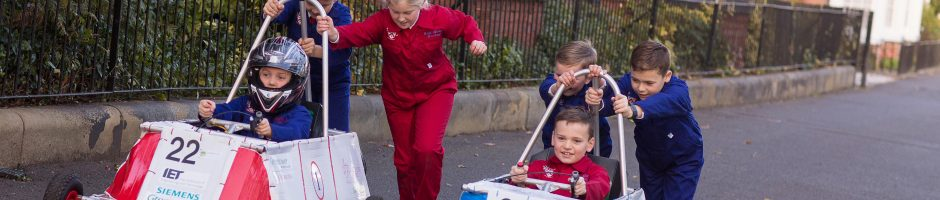 Red House School pupils race their two racing cars outside the school