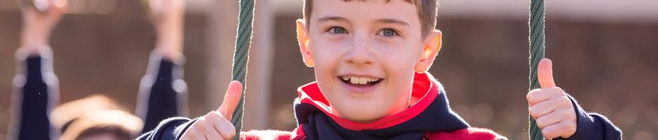 Red House pupil playing outside in the Junior School playground with his thumbs in the air