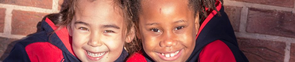 Two Red House School pupils smiling in the Junior School playground