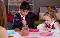 Two Red House School pupils spend time in the Zen Den looking at a jar with coloured powder in it