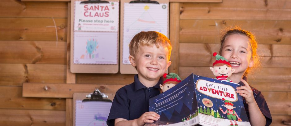 Two Red House School pupils sat at a table in the Nursery garden reading a Christmas book and holding two elf toys