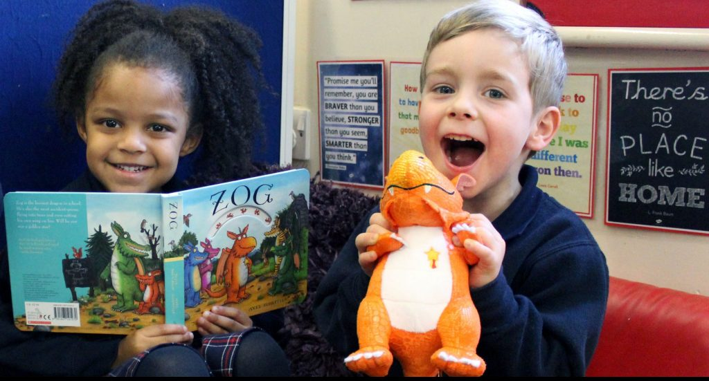 Two Red House School children holding a reading book and toy dragon