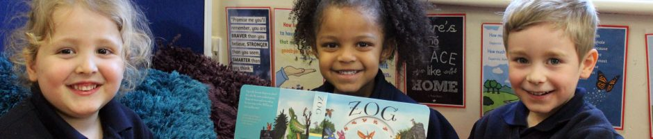 Three Red House School children sitting together with a story book called Zog