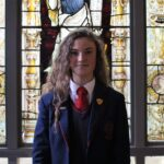 Red House prefect stood by a stained glass window