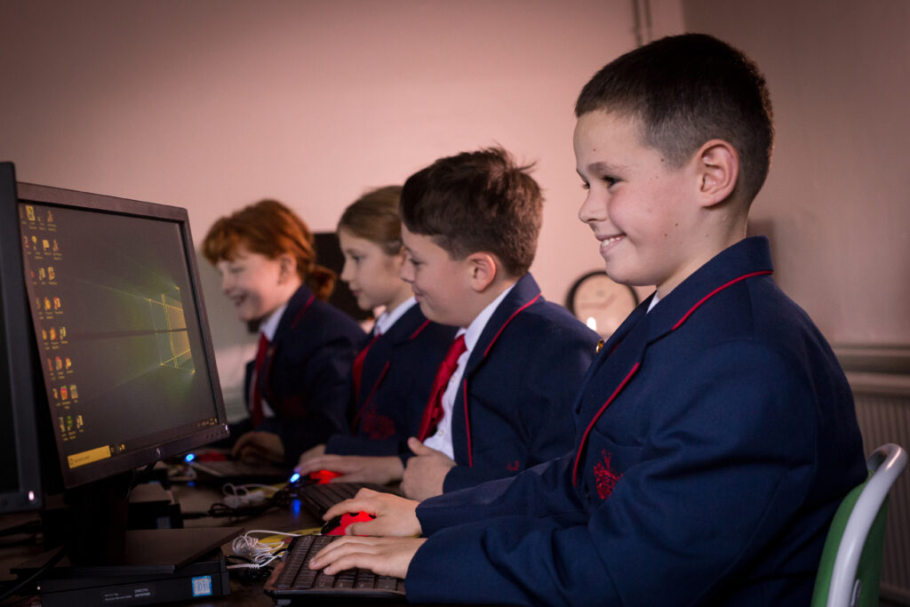 Red House School pupil is sat at a computer in the ICT suite. In the background there is three other pupils working on computers