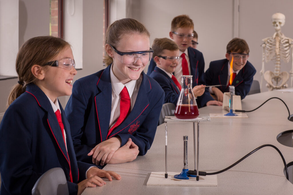 Two girls are conducting a science experiment with a bunsen burner. In the background four boys are also conducting a science experiment.