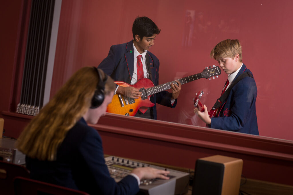 Three pupils are in the Music School. Two boys are playing their guitars in the Recording Studio, whilst a girl is sat with headphones on at the mixing desk.