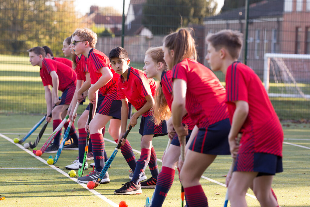 Seven Red House School pupils are in a line holding hockey sticks on the Astroturf.