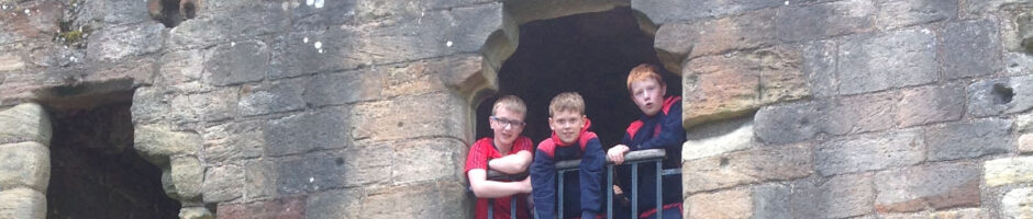 Three Red House School pupils looking out Warkworth Castle