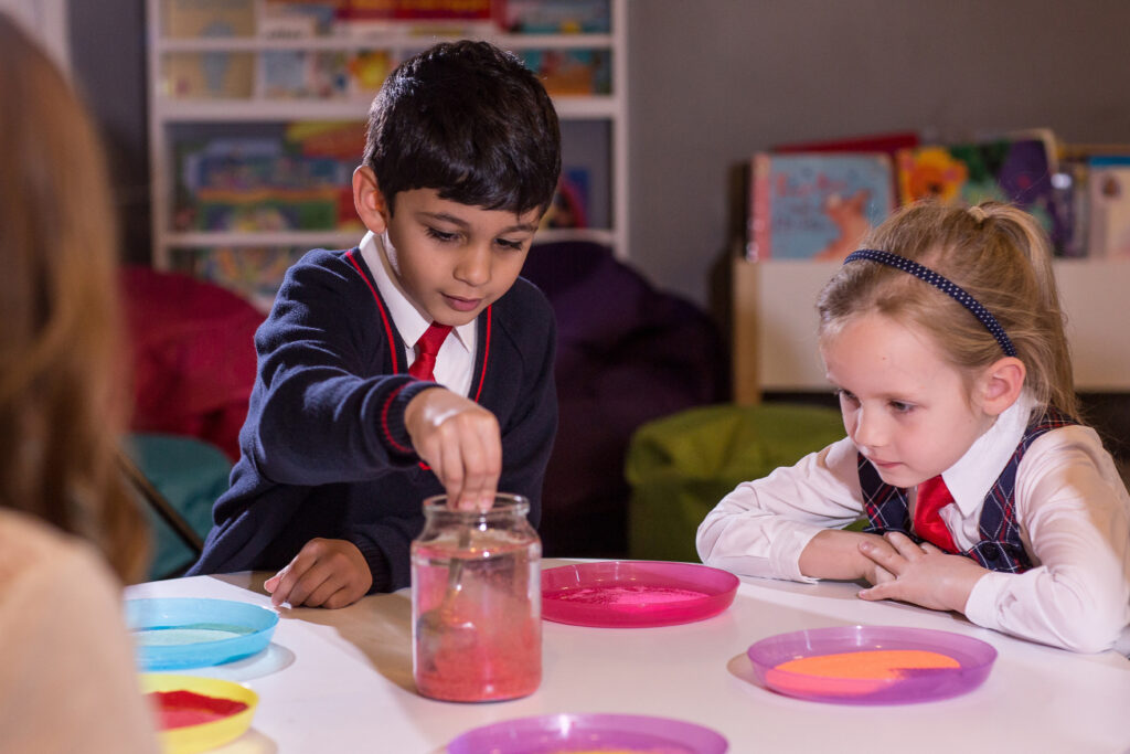 Two Red House School pupils are in the Zen Den looking at a jar full of water and glitter