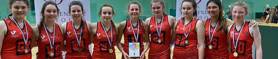 Nine Red House School pupils are stood in a row on a netball court. They were awarded the U14 netball plate winners of the ISA Sport Tournament.