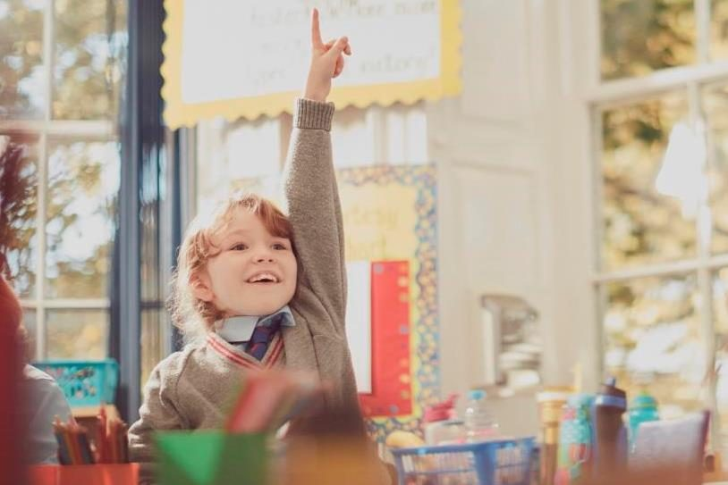 child putting hand in the air in the classroom