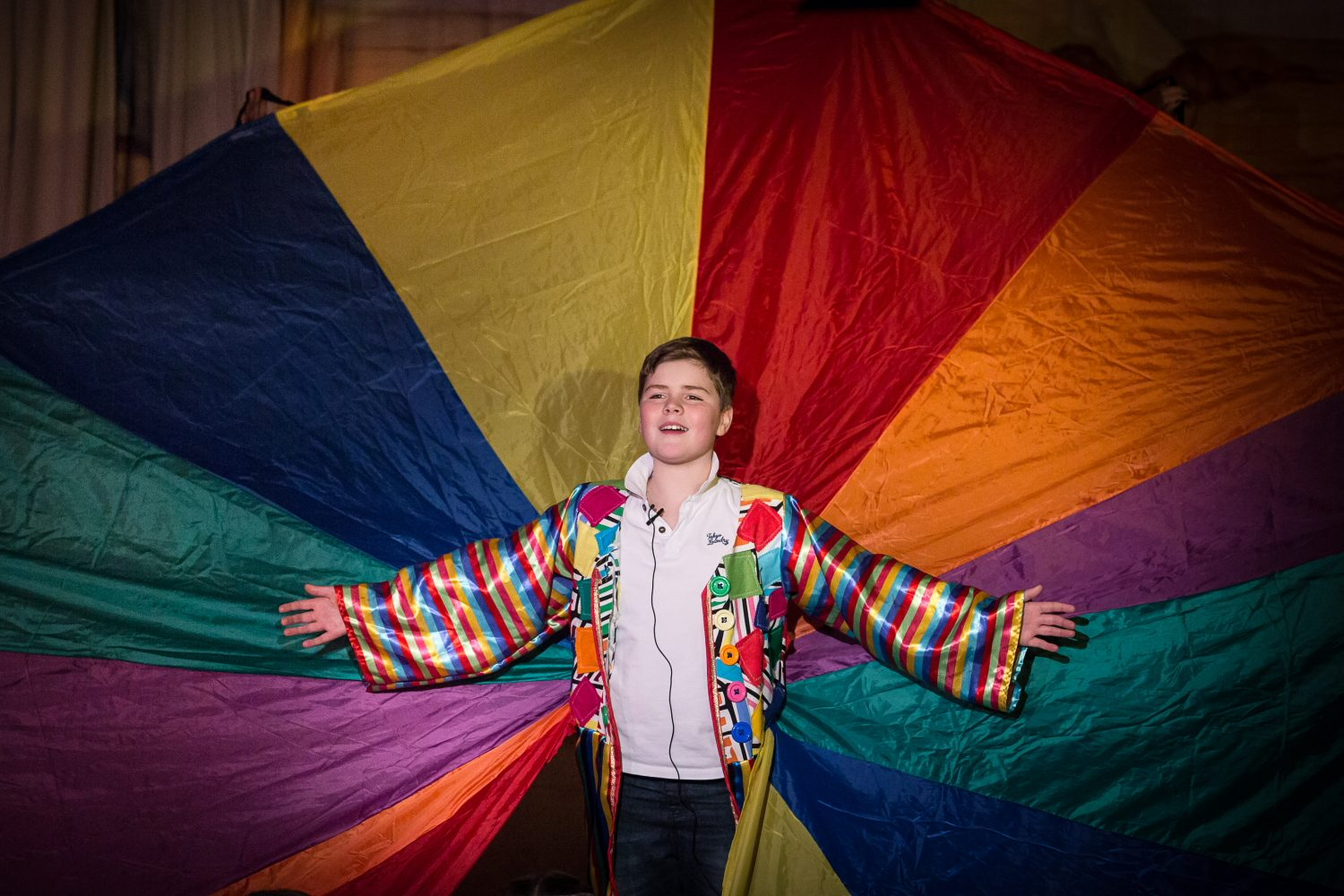 Pupil playing the part of Joseph from the musical Joseph and the amazing technicolor dreamcoat. The coat of many colours is on full display behind the pupil.