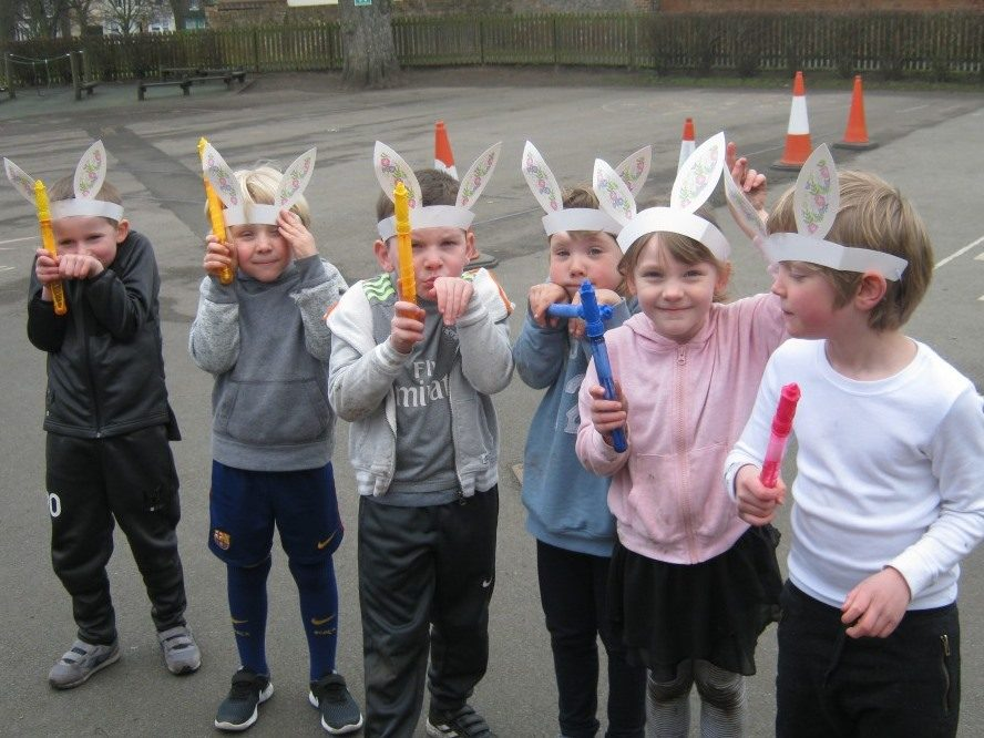 six pupils with bunny ears on their heads stood togther in a line in the Nursery and Infant School playground at Red House School