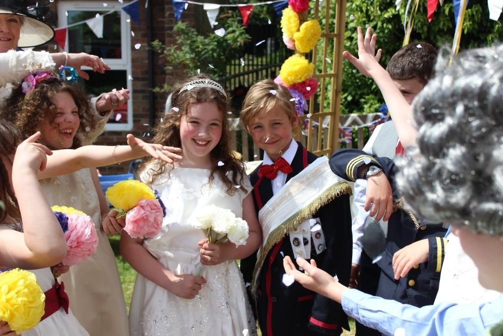Children at Red House School celebrate the Royal Wedding by dressing up as Princess Megan and Prince Harry, whilst other pupils throw wedding confetti in the air .