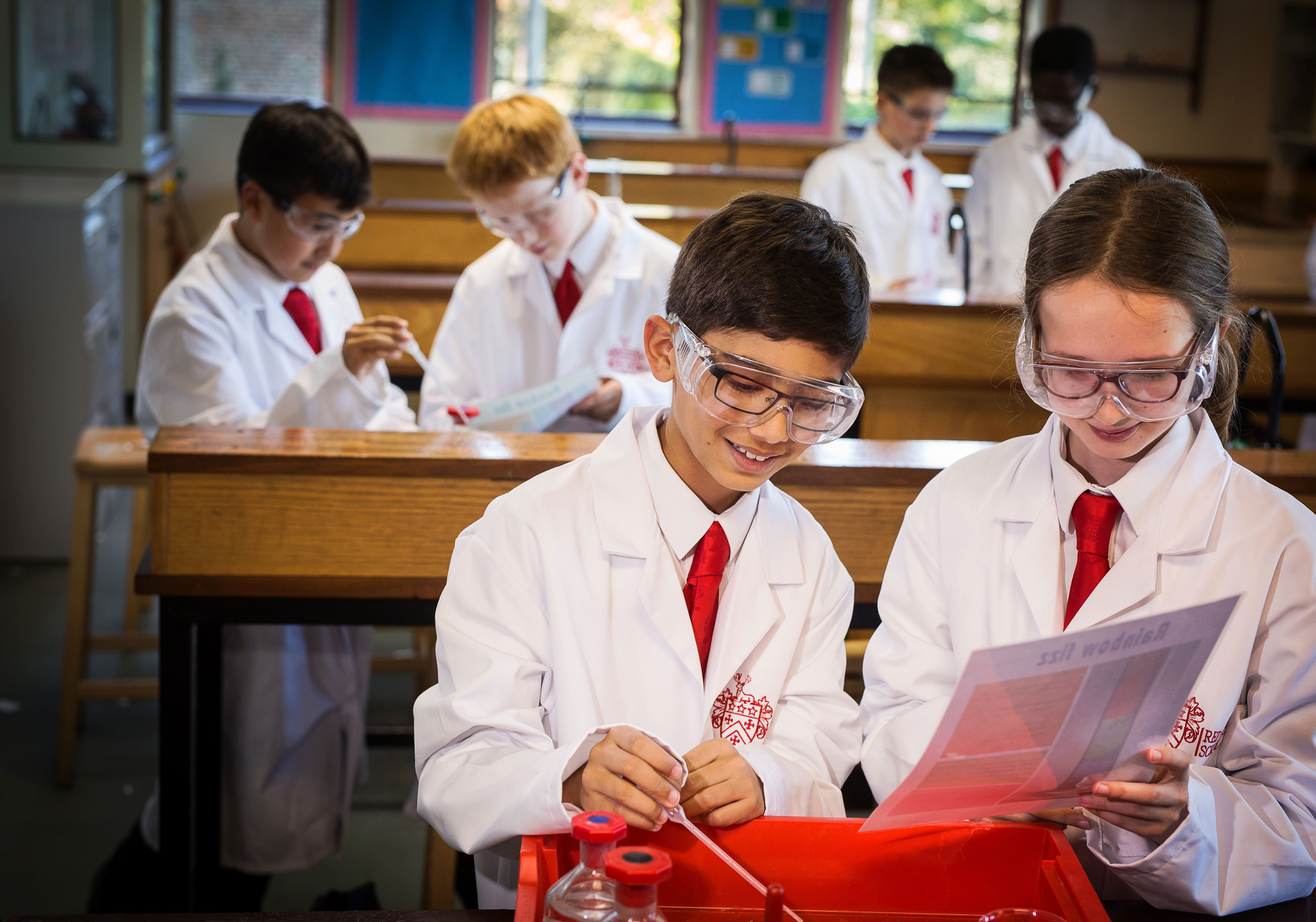 Two Red House School pupils measuring liquids and holding an instructions sheet in a chemistry lesson. There are 4 other pupils in the background taking part in the same experiment