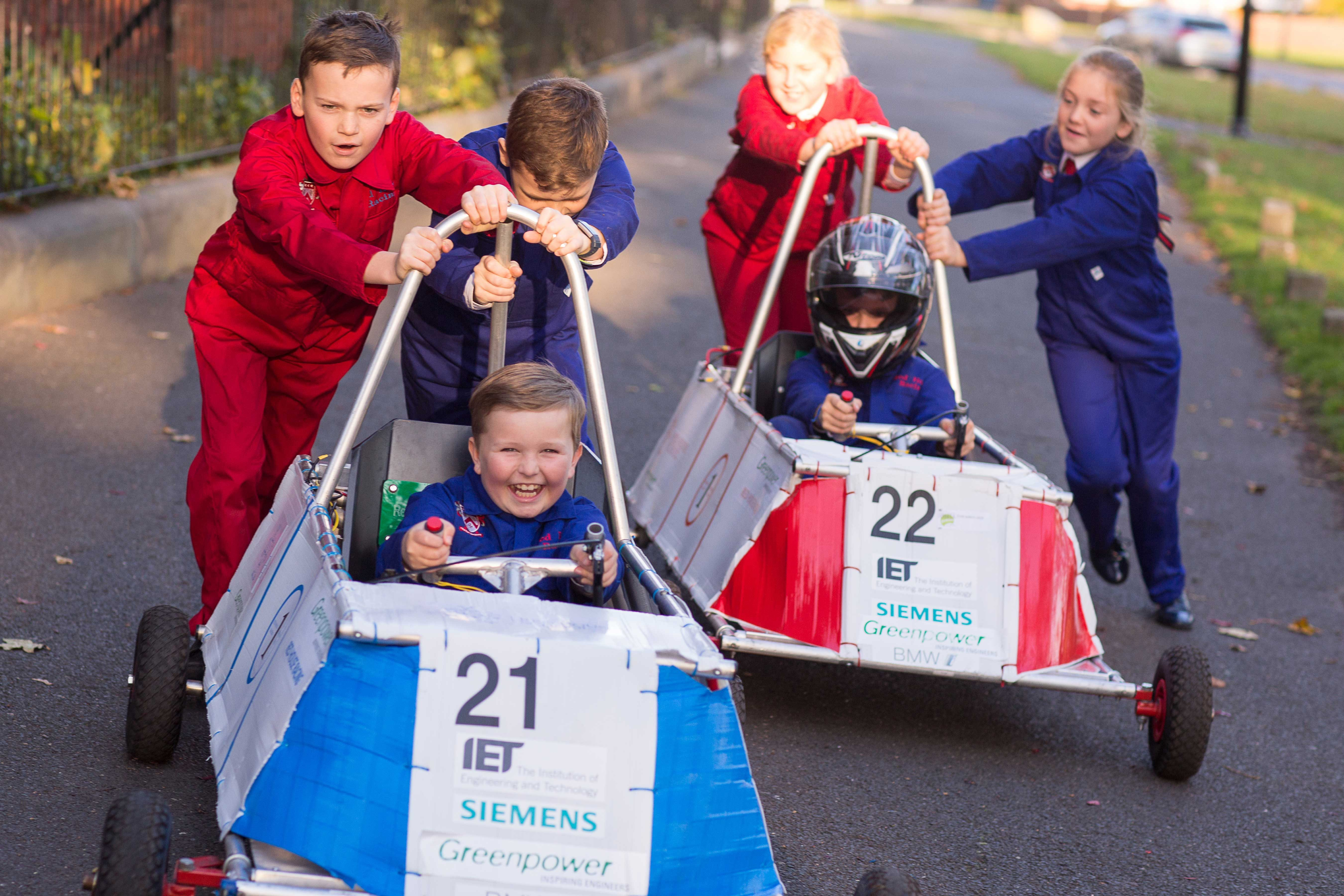 Two pupils sat in racing cars with four pupils pushing the racing cars outside of Red House School in Norton.