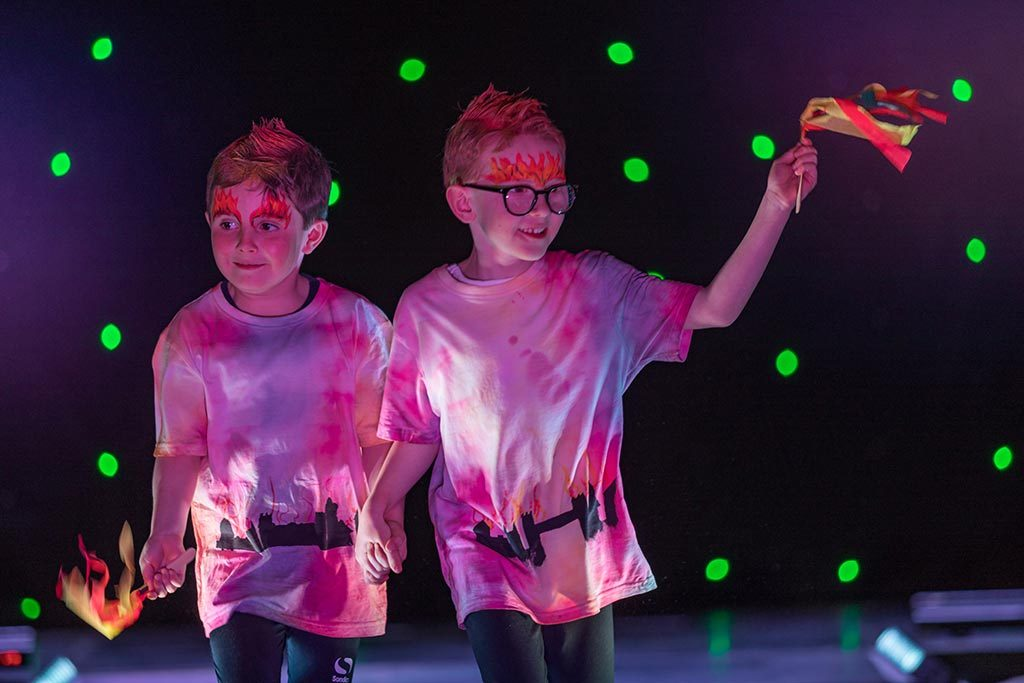 Two Red House School pupils walk down the catwalk at the Red House Fashion Show wearing their designed t.shirts