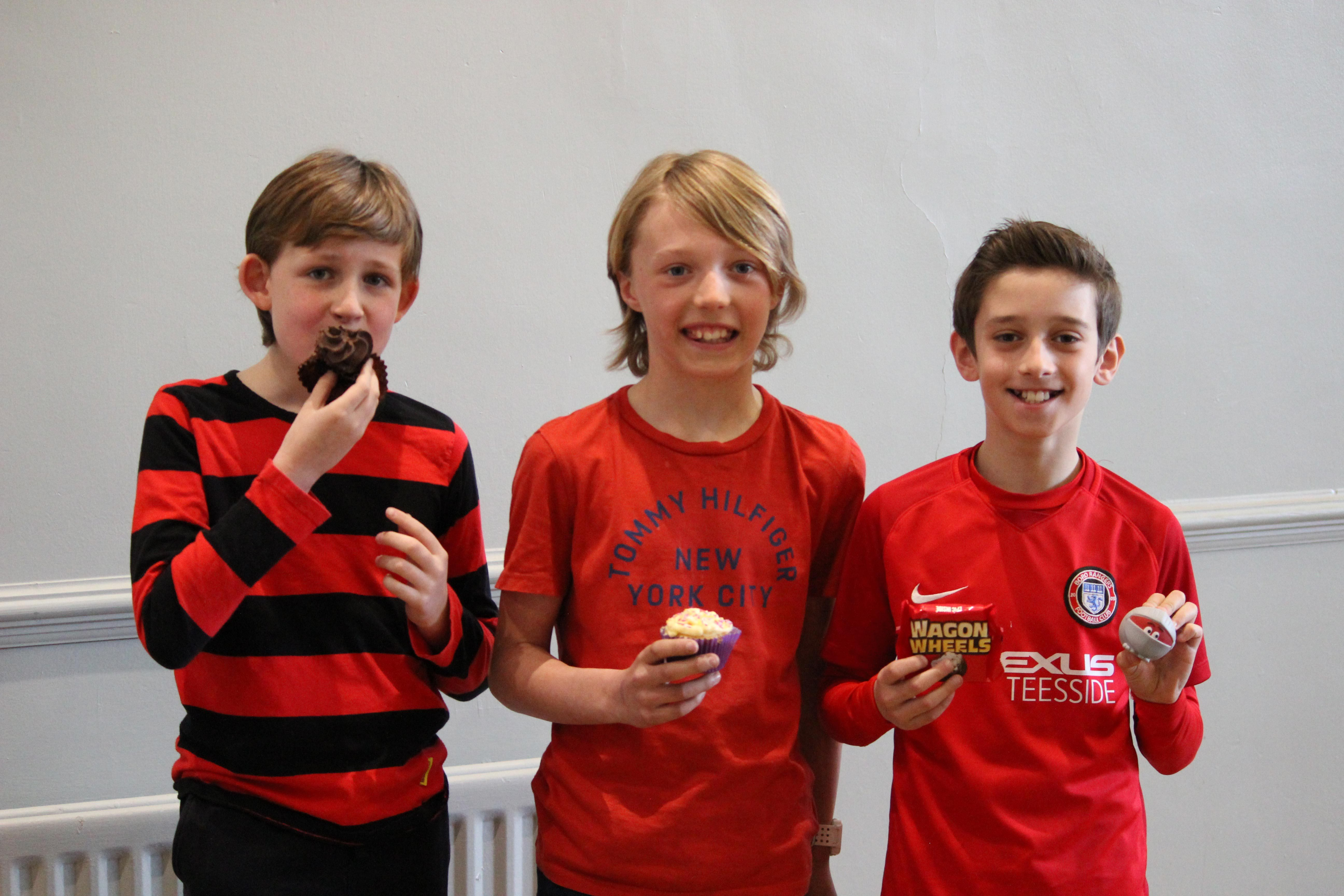 Three Red House School pupils stood holding cakes that they have bought to raise funds for Red Nose Day