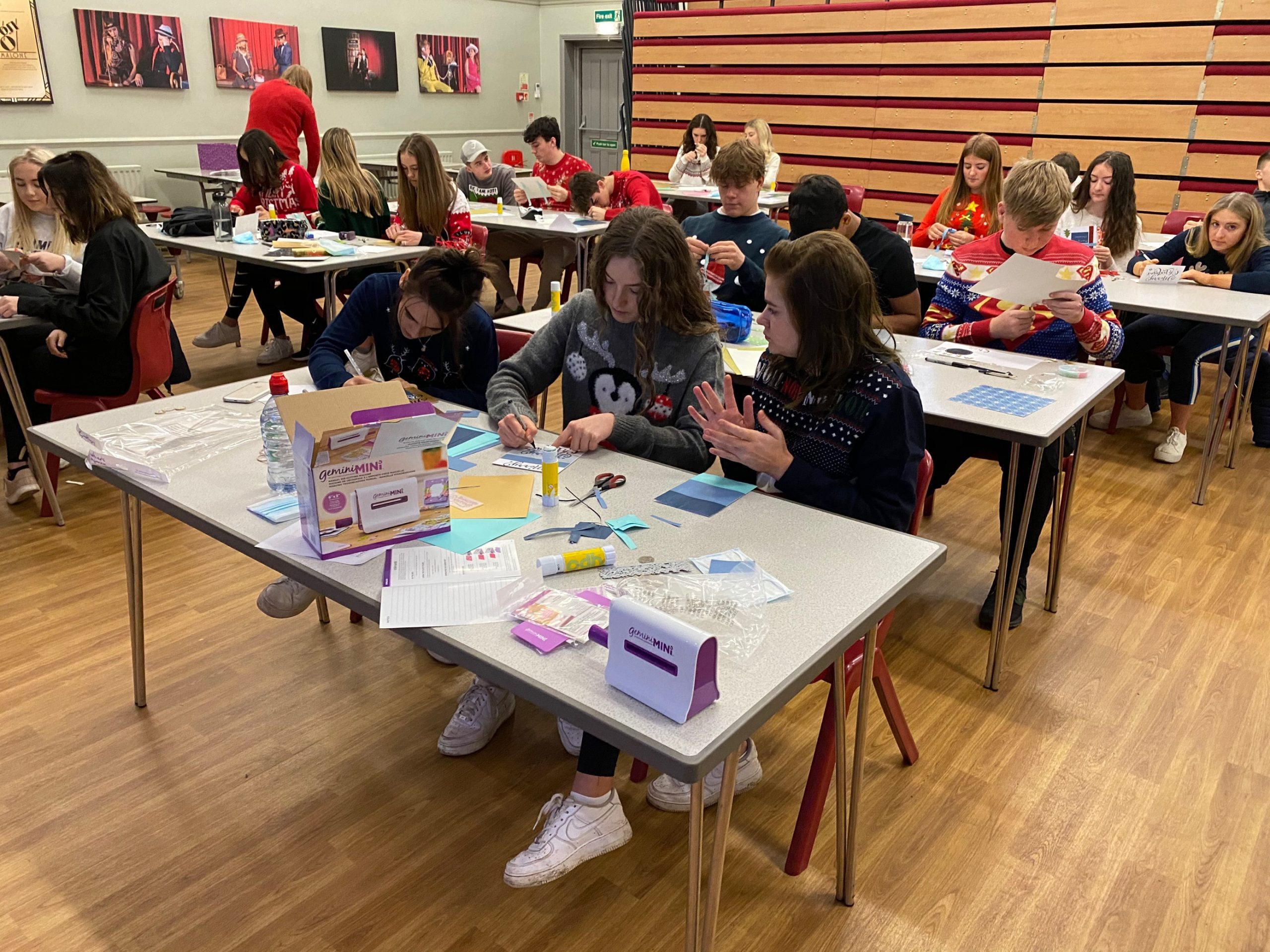 Red House Senior School pupils sit around tables making Christmas crafts.