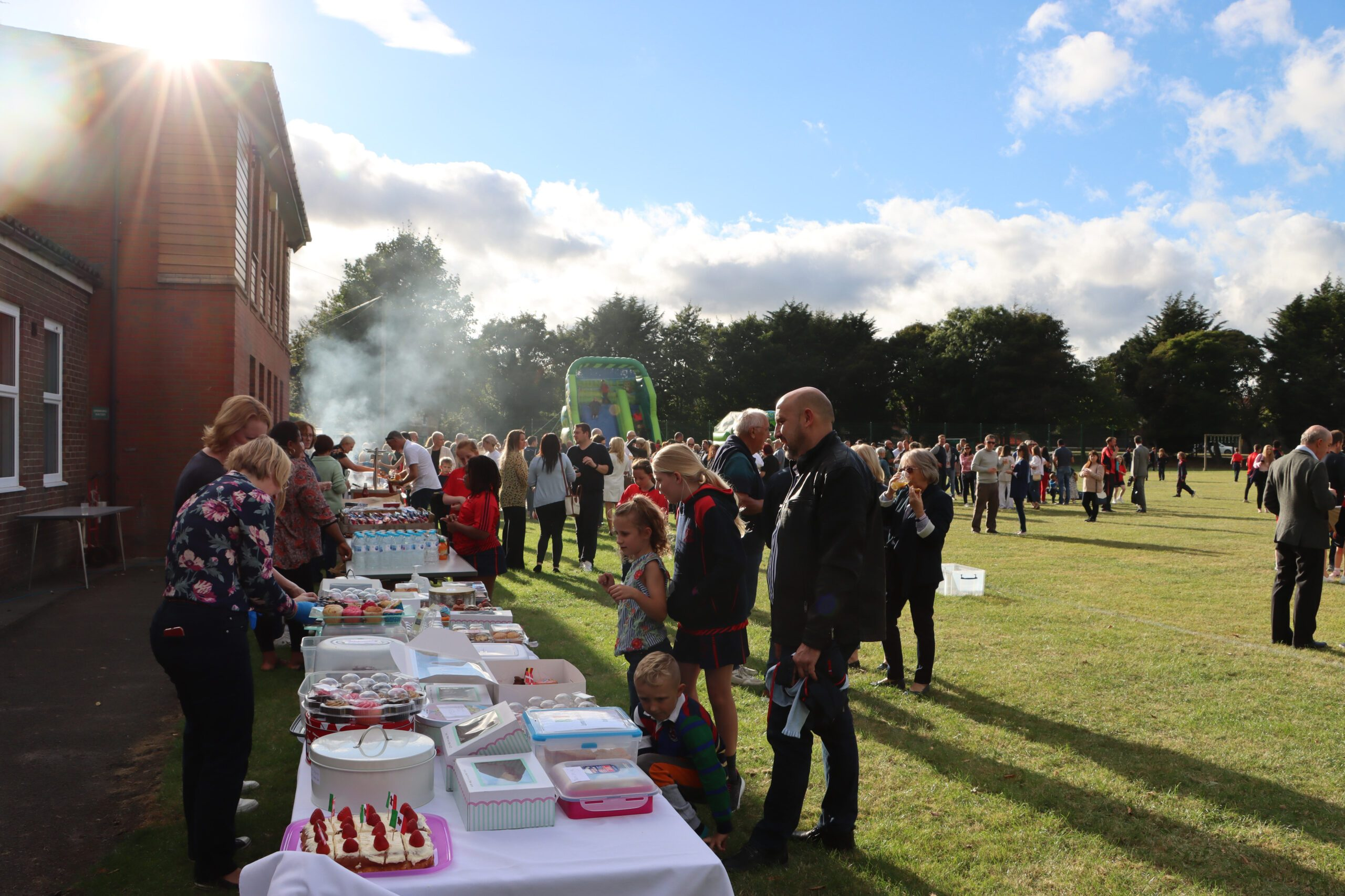 families coming together on the Senior School field at The PTA Welcome BBQ. Food stalls and bouncy castles.